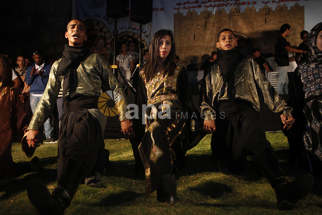 """Palestinians youth participate in dancing of """"Dabka"""" heritage during a celebrate the holy month of Ramadan in Herod's Gate north of the old city of Jerusalem, on July 29, 2013. Muslims around the world are observing the holy fasting month of Ramadan in which they refrain from eating, drinking, sex and smoking from dawn to dusk. Photo by Saeed Qaq"""