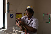 A nurse holds a new born baby in the nursery of the Duncan Hospital in Raxaul, Bihar, India.