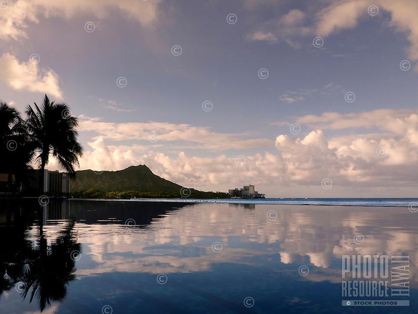 Sunrise over Diamond Head, reflected in peaceful waters at Waikiki, O'ahu.