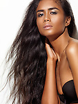 Artistic beauty portrait of a young dark-skinned woman with beautiful long healthy brown hair isolated on white background
