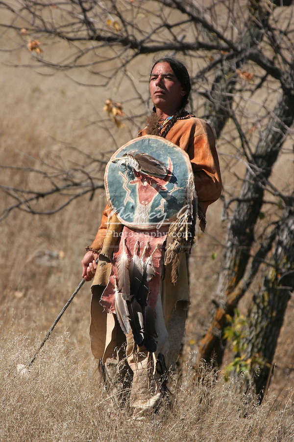 A Native American Indian man standing with a weapon with a shield
