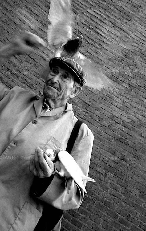 Perpignan (Pyrénées-orientales)<br /> <br /> Homme en train de nourir les pigeons.<br /> <br /> Man feeding pigeons.
