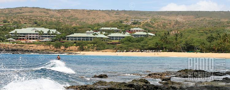 Man surfs Manele Bay with resort in distance