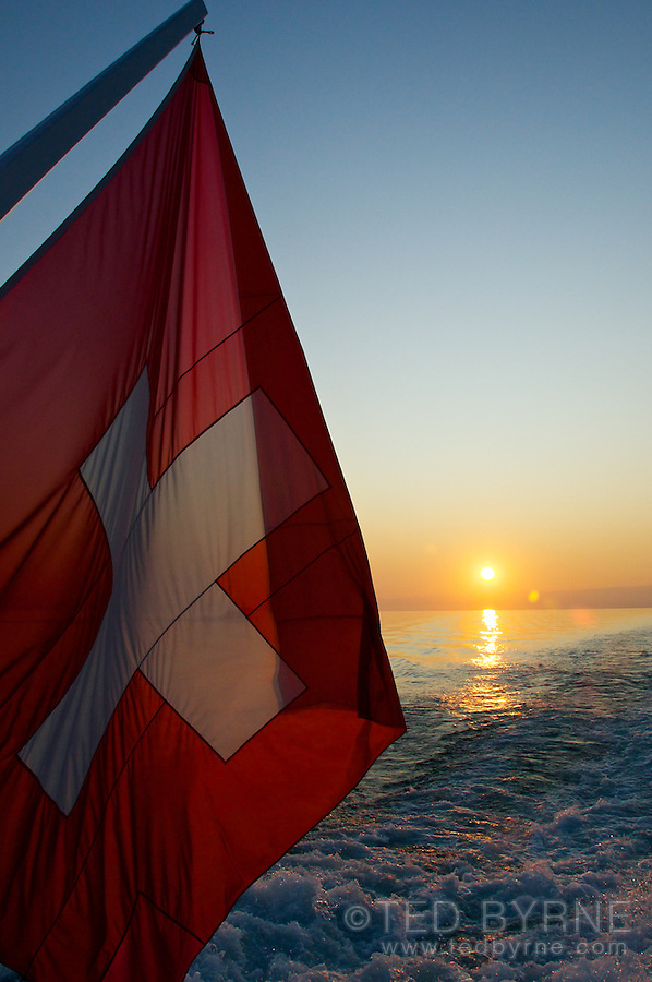 Swiss flag in sunset on the stern of a boat