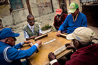 Old Cuban men play dominoes inside the wrecked house in Havana, Cuba, 7 February 2009.