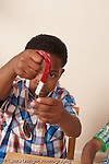6 year old boy playing with magnet picking up metal objects vertical