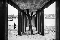 Walking on a River Thames beach underneath a pier on the banks of the River Thames, South Bank, London, England
