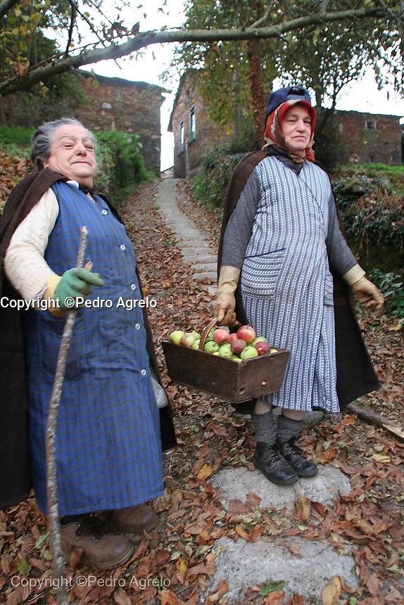 Señoras de una aldea de O Corel con un cesto de manzanas apañadas