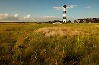 Marsh grasses sway in the breeze near the stately Bodie Island Lighthouse located on Bodie Island on North Carolina's Outer Banks. The light house, built in 1872, stands 156 feet tall and is located on the Roanoke Sound side of the first island that is part of the Cape Hatteras National Seashore. The lighthouse is just south of Nag's Head, a few miles before Oregon Inlet. The conical-shaped lighthouse has white and black bands with a black lantern house. Charlotte NC photographer Patrick Schneider has extensive photo collections of the following lighthouses: Bodie Island Lighthouse, Bald Head Island Lighthouse, Cape Fear Lighthouse, Cape Hatteras Lighthouse, Cape Lookout Lighthouse, Currituck Beach Lighthouse, Diamond Shoal Lighthouse, Federal Point Lighthouse, Oak Island Lighthouse, and Ocracoke Lighthouse on Ocracoke Island.