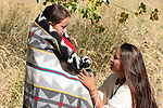 A Native American Sioux Indian mother wrapping an Indian blanket around her young child