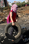 A female Palestinian protester burns tires during clashes with Israeli security forces near the Beit El settlement on the outskirts of Ramallah in the West Bank, on October 16, 2015. The unrest that has engulfed Jerusalem and the occupied West Bank, the most serious in years, has claimed the lives of 34 Palestinians and seven Israelis. The tension has been triggered in part by Palestinians' anger over what they see as increased Jewish encroachment on Jerusalem's al-Aqsa mosque compound. Photo by Shadi Hatem