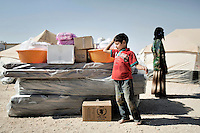 A child and a young woman in a fenced-off area where all new arrivals must stay during initial processing. If they are accepted they will be given one tent per family, a food ration and basic necessities like mattresses and a small cooking set. Approximately two million people have fled the conflict in Syria. At least 130,000 of them live in Zaatari Refugee Camp, although it was designed to house 60,000, and a further 2,000 people arrive each day.