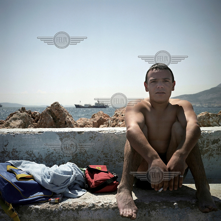 George a young man from Elefsina smokes a cigarette after swimming in the waters of the port of Elefsina. The water around the town is not safe for swimmers as it is heavily polluted by waste from nearby shipyards, oil refineries, cement factories and tanneries.