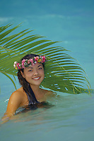Young island girl wearing haku lei in ocean
