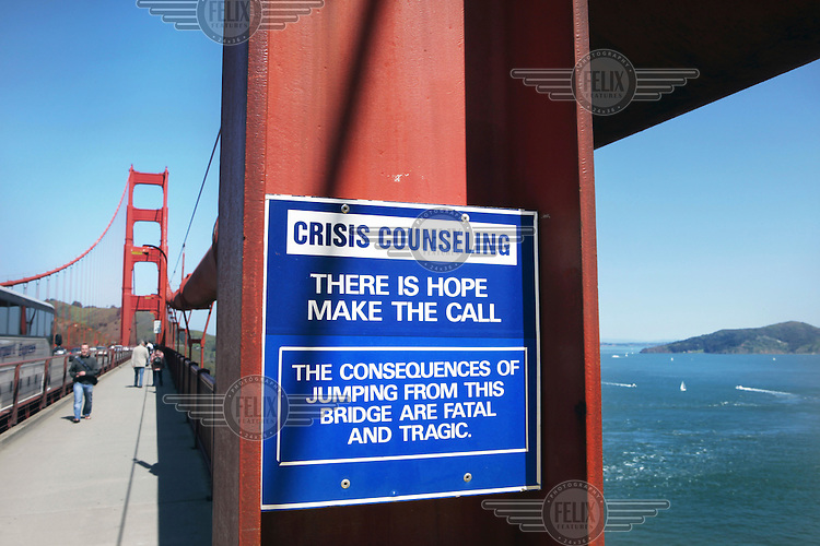 """A sign on the Golden Gate Bridge, San Francisco, California, reads """"Crisis Counseling. There is hope, make the call. The consequences of jumping from this bridge are fatal and tragic""""."""