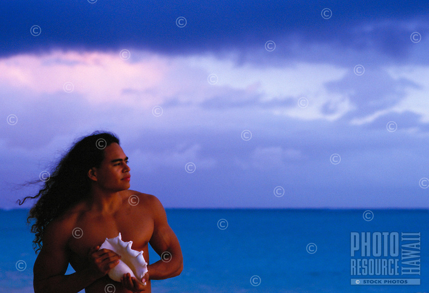 Young Hawaiian man at sunrise with conch shell