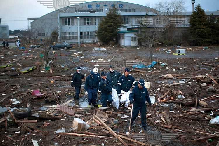 A rescue team carry a body they uncovered from the debris at Sendai airport. On 11 March 2011 a magnitude 9 earthquake struck 130 km off the coast of Northern Japan causing a massive Tsunami that swept across the coast of Northern Honshu. The earthquake and tsunami caused extensive damage and loss of life.