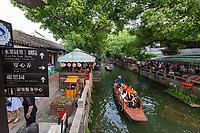 Suzhou, Jiangsu, China.  Chinese Tourists on a Canal in Tongli Ancient Town near Suzhou, a popular weekend tourist destination.  Restaurants line the canal.