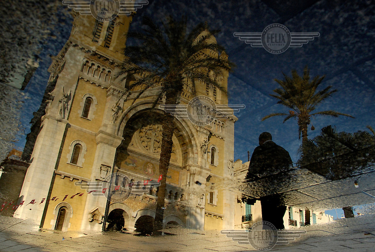The French colonial era cathedral Saint Vincent de Paul is reflected in a puddle on Avenue Bourguiba in the Ville Nouvelle (New Town) area of the city.