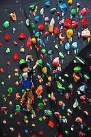A youngster ponders his next move on a colorful outdoor climbing wall.