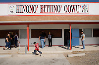 "Jerrad Friday Jr., 3, hops parking blocks in front of the new Arapaho Language Lodge building at its inauguration on the Wind River Indian Reservation in central Wyoming, Friday, Oct. 3, 2008. Northern Arapaho tribal leaders hope the inauguration of the larger new Arapaho Language Lodge immersion school at the reservation will help kids find a better cultural identity and strengthen them better succeed in education. The sign on the building translates directly to ""Arapaho Language Lodge."" (Kevin Moloney for the New York Times)"
