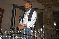 In the wine tasting room, Pascal Delbec, owner and wine maker pouring wine in glasses for tasting  Chateau Belair (Bel Air) 1er premier Grand Cru Classe  Saint Emilion  Bordeaux Gironde Aquitaine France