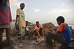 A group of Fulani boys grill fresh fish on a makeshift grill next to a beachside fish market in Dakar, Senegal.