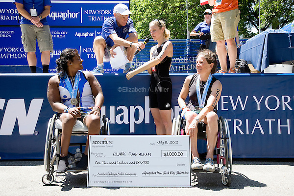 Second and third place finishers Minda and Liz McTernan look on as winner Clare Cunningham is interviewed during the Awards Ceremony after the Aquaphor New York City Triathlon in New York on July 8, 2012.
