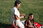 Native American Indian woman braiding the hair of a child