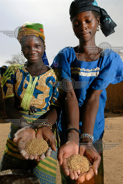 Nana Badama (left) and Hinda Salha (right) from Dan Saga village hold grains of millet in their outstretched hands.