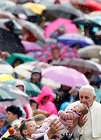 Papa Francesco bacia una bambina al suo arrivo all'udienza generale del mercoledi' in Piazza San Pietro, Citta' del Vaticano, 9 ottobre 2013.<br />