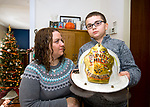 TORRINGTON, CT-122717JS02----Lori Pepler,  wife of  late Torrington Fire Department Deputy Chief, Chris Pepler, looks on as their son Nathan, 10, holds his father helmet at their Torrington home Thursday. Jim Shannon Republican-American
