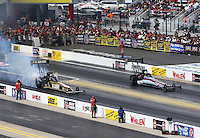 Sep 15, 2013; Charlotte, NC, USA; NHRA top fuel dragster driver Tony Schumacher (left) smokes the tires alongside Leah Pruett during the Carolina Nationals at zMax Dragway. Mandatory Credit: Mark J. Rebilas-