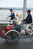 VIETNAM, Hue, a food vendor bicycles his wife across the Perfume river in the early morning