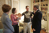 United States President George W. Bush and first lady Laura Bush visit with United States Army Sergeant Adam Replogle of Salida, California, his wife Nicoleta and their 11-month-old daughter Sara at the Fisher House at Walter Reed Army Medical Center in Washington, D.C., December 21, 2004. Sergeant Replogle was injured while serving in Operation Iraqi Freedom. <br /> <br /> <br /> Mandatory Credit: Paul Morse / White House via CNP