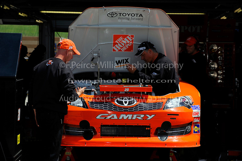 Working on the car of Joey Logano, (#20) Home Depot Camry, in the garage.