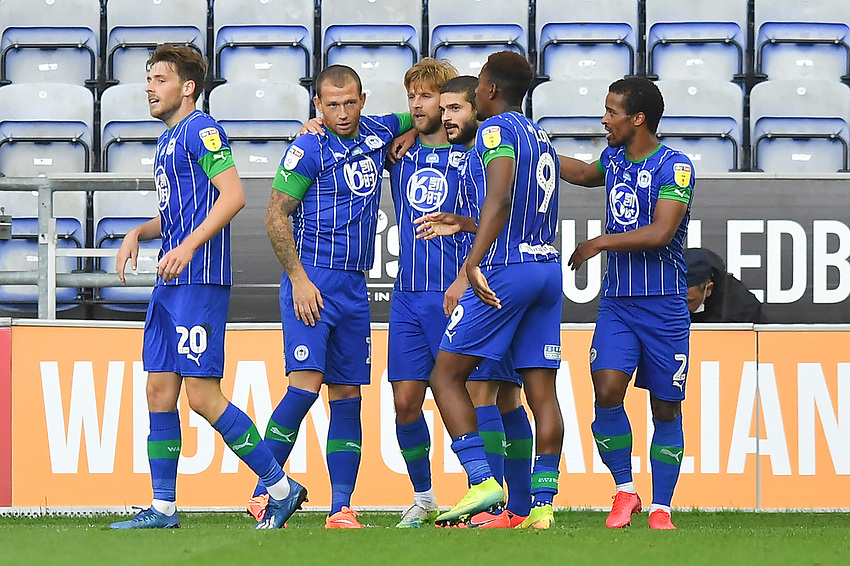 Although social distancing should be observed in celebrations, Michael Jacobs is hugged by team mates after scoring his team's second goal<br /> <br /> Photographer Dave Howarth/CameraSport<br /> <br /> The EFL Sky Bet Championship - Wigan Athletic v Blackburn Rovers - Saturday 27th June 2020 - DW Stadium - Wigan<br /> <br /> World Copyright © 2020 CameraSport. All rights reserved. 43 Linden Ave. Countesthorpe. Leicester. England. LE8 5PG - Tel: +44 (0) 116 277 4147 - admin@camerasport.com - www.camerasport.com