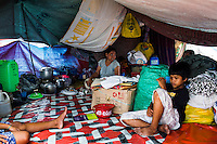 Survivors of the Zamboanga City rebel attack cook lunch in their shared evacuee's tent in the city's largest stadium in Zamboanga, Mindanao, The Philippines on November 4, 2013. These Internally Displaced People (IDP) have set up shared tents along the running track and in the breachers in this stadium after surviving the 3 week long attack by MNLF rebels. Photo by Suzanne Lee for SPRINT-IPPF