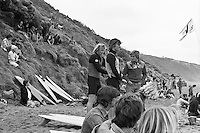 Spectators on the cliffs and on the beach  during the  running of the 1976 Rip Curl Pro, Bells Beach, Torquay, Victoria, Australia. Easter 1976. Surfboard shaper Simon Anderson (AUS) and founder of Ocean & Earth Brian Cregan (AUS) prepare for thier heat..Photo:  joiliphotos.com