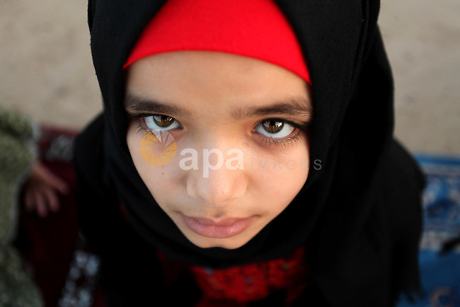 A Palestinian girl attends the morning prayer of the Muslim holiday of the Eid al-Adha on September 12, 2016, in Khan Younis in the southern Gaza strip. Muslims across the world celebrate the annual festival of Eid al-Adha, or the festival of sacrifice, which marks the end of the Hajj pilgrimage to Mecca and commemorates prophet Abraham's readiness to sacrifice his son to show obedience to God. Photo by Ashraf Amra