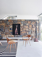 A wall faced with natural stone makes an interesting feature in the spacious living room.