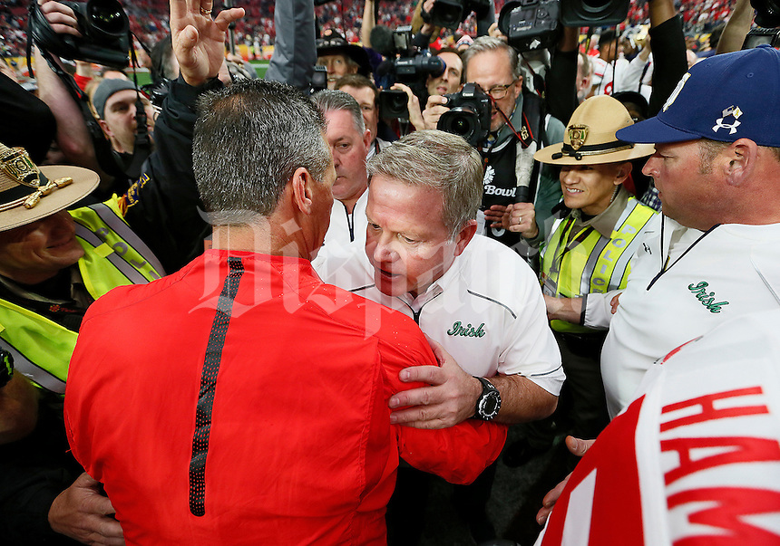 Ohio State Buckeyes head coach Urban Meyer talks to Notre Dame Fighting Irish head coach Brian Kelly at mid-field following Ohio State's 44-28 win over the Notre Dame Fighting Irish in the Battlefrog Fiesta Bowl at University of Phoenix Stadium in Glendale, Arizona on Jan. 1, 2016. (Adam Cairns / The Columbus Dispatch)