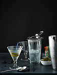 A full martini glass with small pickles on a blue toothpick, glass of ice, strainer, stainless steel mixing cup, dish of pickles, spoon, toothpicks, and empty martini glass. On slate surface with black background