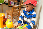 Education preschool 3-4 year olds pretend play boy in kitchen area wearing hat talking to himself and looking to side horizontal