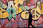 Pedestrian eyeing a graffiti wall in Copenhagen, Denmark
