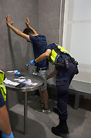 Switzerland. Canton Ticino. Bellinzona. Railway station. Police station. A police officer from TPO (Transport Police) is strip searching an Italian man who had no valid ticket while travelling on a train. The man was brought by the policemen to the police station in order to control the person's identity. His wallet and identity document are on the table.The Italian man was fined and 15 minutes later sent free out the police station. TPO (Transport Police) is the Swiss Federal Railways Police. Swiss Federal Railways (German: Schweizerische Bundesbahnen (SBB), French: Chemins de fer fédéraux suisses (CFF), Italian: Ferrovie federali svizzere (FFS)) is the national railway company of Switzerland. It is usually referred to by the initials of its German, French and Italian names, as SBB CFF FFS. A strip search is a practice of searching a person for weapons or other contraband suspected of being hidden on their body or inside their clothing by requiring the person to remove some or all of his clothing. The strip search is a mandatory procedure which requires legal authority. It is done by a police officer once a person is arrested and locked in a cell. A police station or station house is a building which serves for police officers. The building contains temporary holding cells and interview/interrogation rooms 19.07.2017 © 2017 Didier Ruef