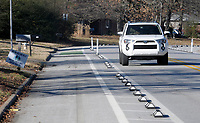 NWA Democrat-Gazette/DAVID GOTTSCHALK  The temporary bike lanes are visible on Rolling Hills Drive Wednesday, January 9, 2019, as traffic passes by in Fayetteville. BikeNWA, a regional bicycling advocacy organization, installed the temporary protected bike lanes at Rolling Hills Drive in November as part of a larger pilot project including Springdale and Eureka Springs paid for through a grant from the Walton Family Foundation.