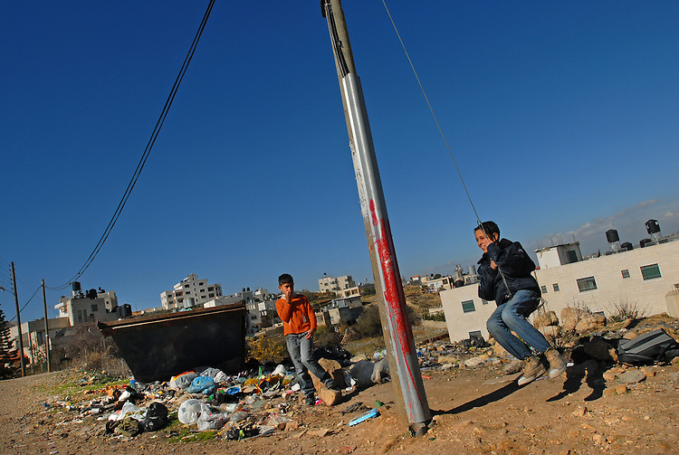 Kids, one of them swings on a telephone cable, play at the entrance to the Palestinian refugee camp of Jelazun, West Bank.