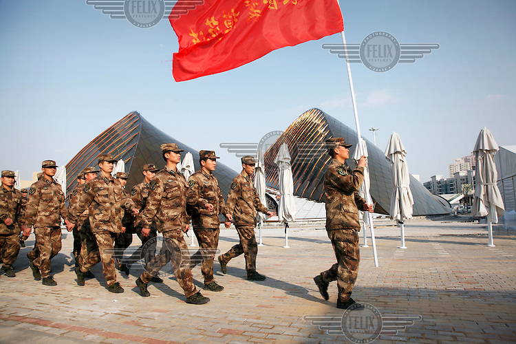 Chinese People's Liberation Army soldiers walk, in file, through the grounds of the 2010 World Expo site.