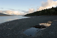 Very early light over Lake Te Anau, South Island, is reflected in the puddles on a pebble beach.